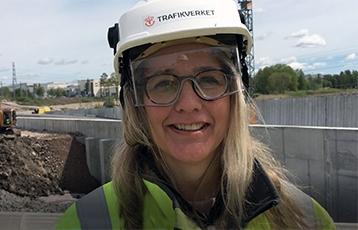 Kvinna i ljust hår, skyddsglasögon och vit hjälm står framför en byggarbetsplats.